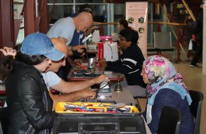 Shamsa Kassim, right, speaks with a volunteer. She came to the cafe to have an iron repaired. (Photo: The Sheridan Sun)